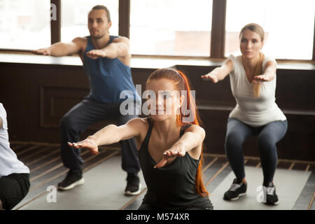 Sporty young people doing squat exercise at group fitness traini - Stock Photo