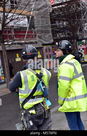 construction workers wearing high visibility jackets and hard hats or safety helmets and harnesses talking or discussing - Stock Photo