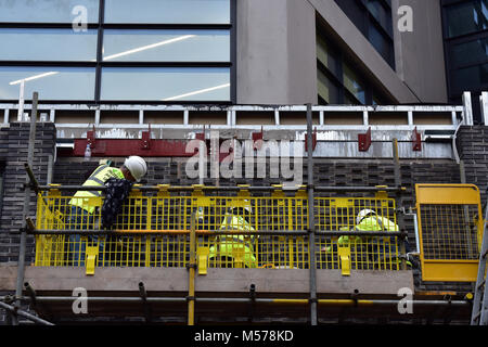 Construction workers werring high visibility clothing in a cradle or winch hoist cage fitting windows on a new build - Stock Photo