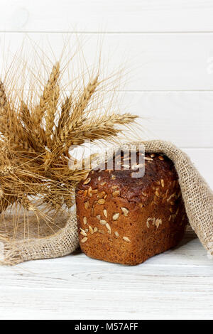 Bread with seeds and wheat ears on wooden table. - Stock Photo