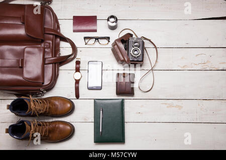 Still life with Men's casual outfits with leather accessories on brown wooden background, beauty and fashion, travel - Stock Photo