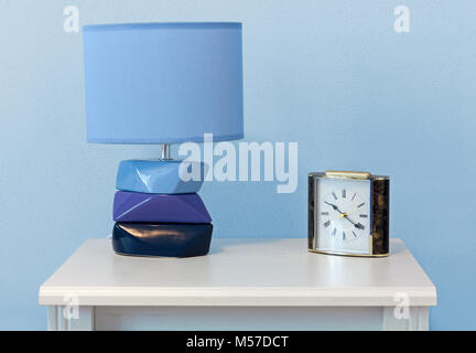 A modern lamp and a classic alarm clock on a white wooden nighstand - Stock Photo