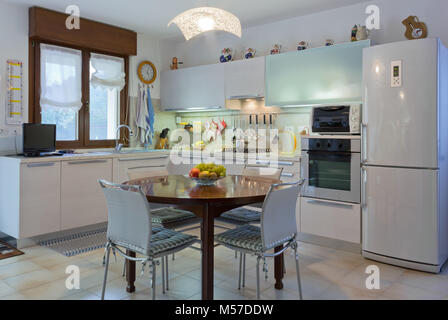 Italian modern white home kitchen interior with round wooden table and tiled floor - Stock Photo
