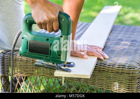 Woman sawing wooden plank with electric saw - Stock Photo