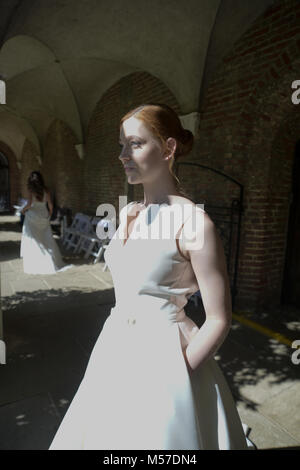 Beautiful Models wearing Bridal wear are walking on a catwalk at Herstmonceux Castle- it is a bright and Sunny day - Stock Photo