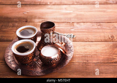 Antique bronze pitcher and coffee cup set with dates in a tray isolated on a white background,Turkish coffee set - Stock Photo