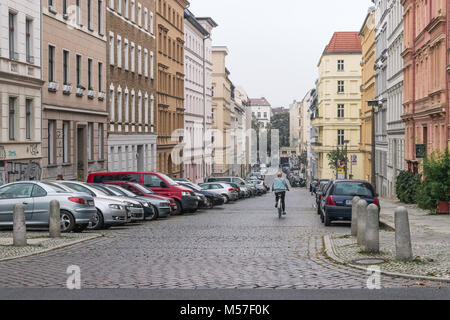 BERLIN - OCTOBER 18, 2016: A girl on a bike rides down a beautiful street in Berlin, Germany - Stock Photo