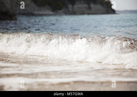 Coastal transparent sea ocean crashing wave with foam on its top,Sandy beach and the waves of the Mediterranean - Stock Photo