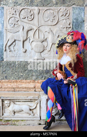 A beautiful harlequin playing the mandolin outside Saint Mark's Basilica during the Carnivel of Venice (Carnevale - Stock Photo