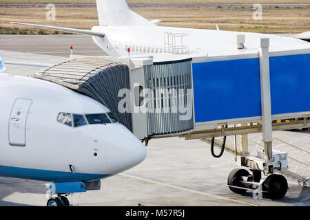 Jetway is served to passenger airplane at airport. Close up. Preparation for departure, boarding passengers on board. - Stock Photo