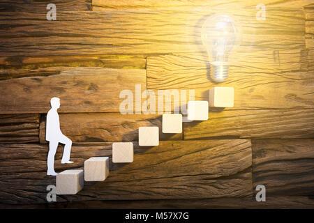 Closeup of paper businessman climbing block ladder leading towards illuminated light bulb on wood - Stock Photo