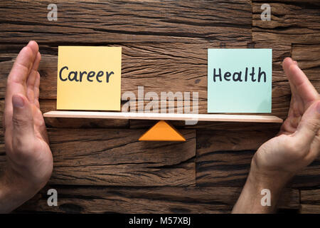 Closeup of hands covering balance between career and health on seesaw against wood - Stock Photo