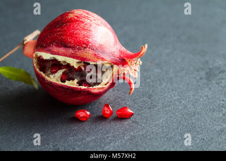 Ripe red fruit pomegranate with seeds on black stone background. close-up photo shallow depth of field - Stock Photo