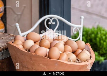 pink pottery basket filled with eggs - Stock Photo