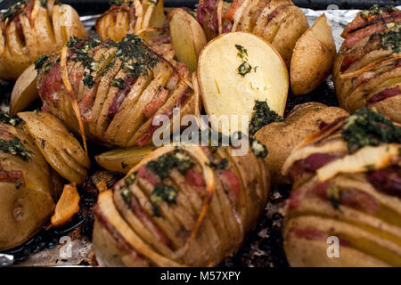 Potato.Roasts potatoes. Home cooking. Baking pan full of baked potatoes stuffed with bacon sausage onions and grated - Stock Photo