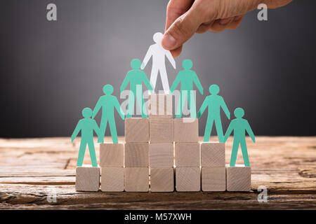 Closeup of hand placing paper businessman with employees on pyramid blocks - Stock Photo