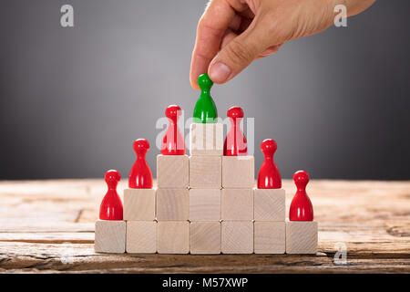 Closeup of hand placing green pawn with other red figurines on pyramid blocks - Stock Photo