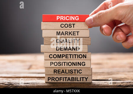 Closeup of hand building pricing concept with wooden blocks on wood - Stock Photo