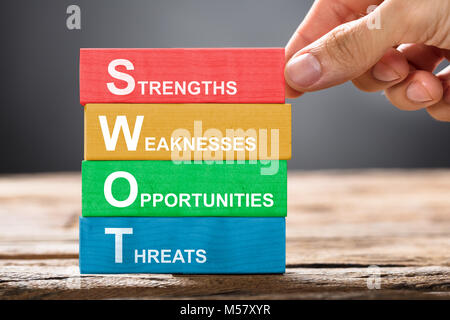 Closeup of hand building colorful SWOT concept with wooden blocks on wood - Stock Photo