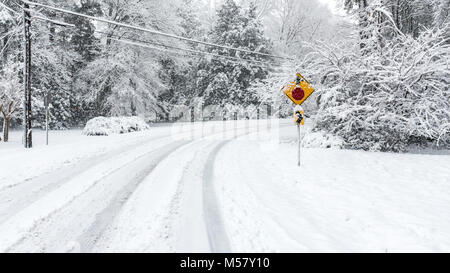 Stop sign on snow covered road iwth trees and telephone pole - Stock Photo