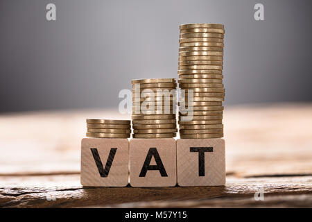 Closeup of VAT text written on wooden blocks with stacked coins - Stock Photo