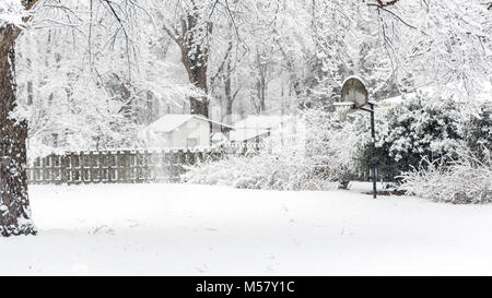 Basketball backboard covered in snow in yard with fence and shack in the background - Stock Photo