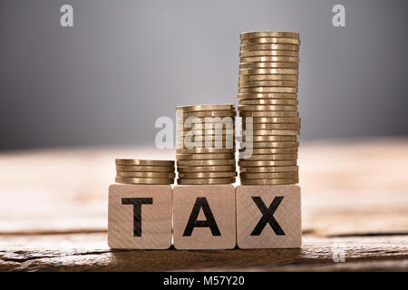 Closeup of tax text written on wooden blocks with stacked coins - Stock Photo