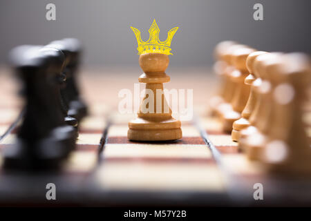 Closeup of pawn with king crown amidst chess pieces on board game representing leadership - Stock Photo