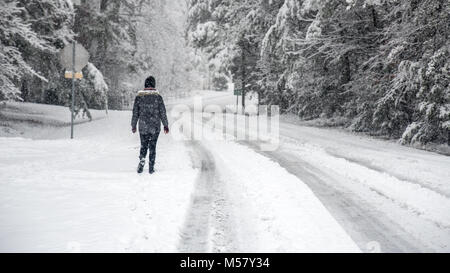 Woman walking down the street with trees covered with snow, street signs and road with tire tracks - Stock Photo