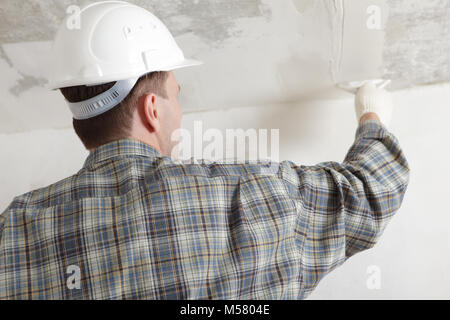 Construction worker in white hardhat plastering the ceiling - Stock Photo