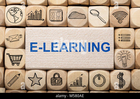 Full frame shot of e-learning text on wooden block surrounded by various computer icons - Stock Photo