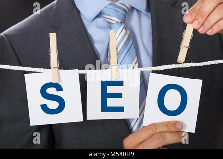 Closeup midsection of businessman pinning SEO cards on clothesline - Stock Photo