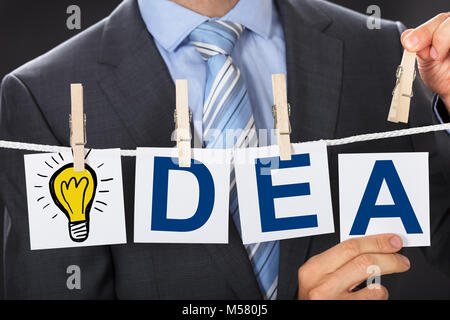 Closeup midsection of businessman pinning IDEA cards on clothesline - Stock Photo