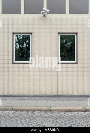 Two cameras at a facade observating the sidewalk in the Alte Jacobstraße in Berlin, Germany. - Stock Photo