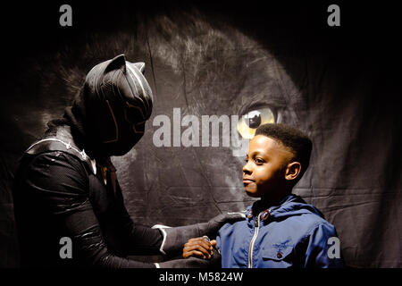 London UK 17th Feb 2018 A young boy shakes hands with a man dressed as Marvel's first lead black superhero Black - Stock Photo