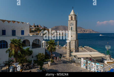 The  clock tower and the entrance to the port of Symi (or Simi), a tiny island of Dodecanese, in Greece. - Stock Photo
