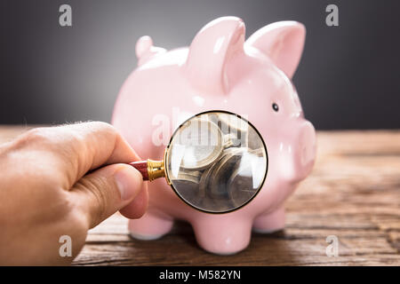 Cropped image of businessman examining coins in piggybank with magnifying glass on wooden table - Stock Photo