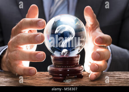 Midsection of businessman covering crystal ball with smoke forming question mark at wooden table - Stock Photo