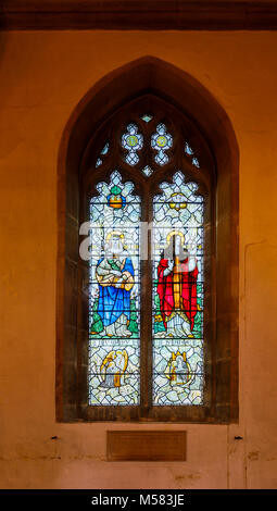 Sightseeing: Colourful stained glass window inside the parish church of St Mary in Painswick, an unspoilt village - Stock Photo