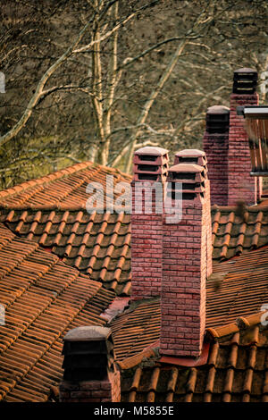 Traditional Roofs and Chimneys of brinks in Greece - Stock Photo