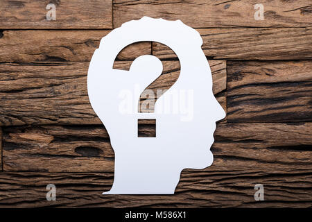 Directly above shot of paper businessman's head with question mark on wooden table - Stock Photo