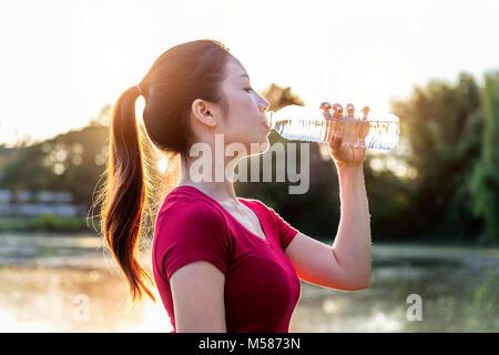 Sporty woman drinking water on sunlight. - Stock Photo