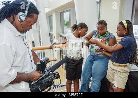Black woman mother parent man girl girls student contestant family video camera media - Stock Photo