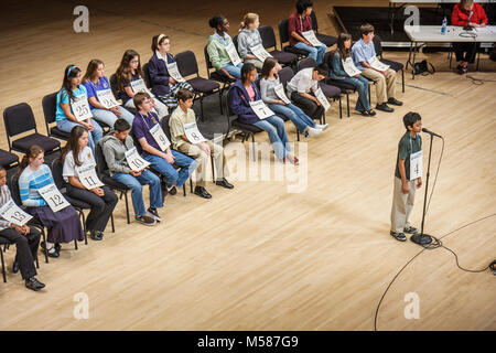 Black Hispanic Asian ethnic mix boy girl teen students contestant numbered tag stage microphone eventual winner - Stock Photo