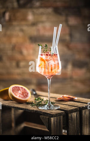 Cocktail drink on a old  wooden board. Alcoholic beverage with tropical fruits red pepper herb and ice. - Stock Photo