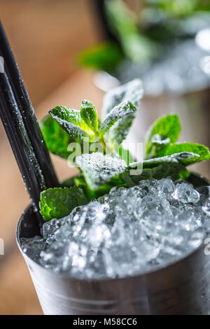 Mint julep cocktail alcoholic drink on wooden board in pub or restaurant. - Stock Photo