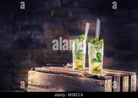 Mojito. Alcoholic cocktail drink mojito on wooden board in pub or sestaurant. - Stock Photo