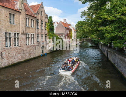 Sightseeing boat tour on the tree-lined Groenerei canal, in Bruges, Belgium - Stock Photo