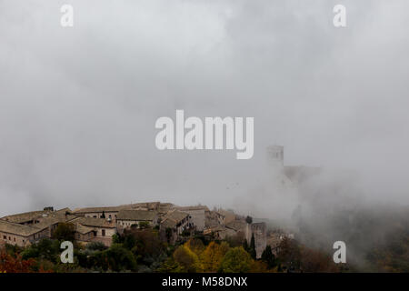 View of St. Francis papal church in Assisi (Umbria, Italy) in the middle of lifting morning fog - Stock Photo