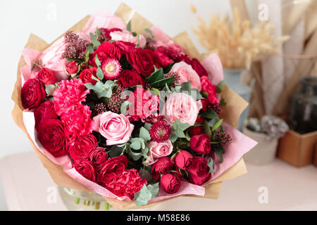 Close-up beautiful luxury bouquet of mixed red and pink flowers in glass vases. the work of the florist at a flower - Stock Photo